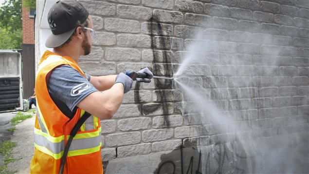 Un employé de la Ville de Montréal nettoie un graffiti.