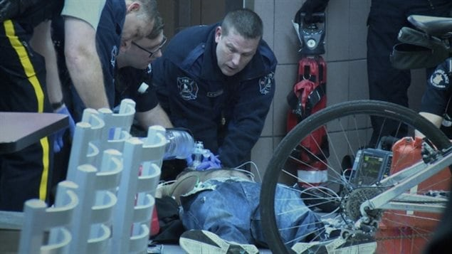 First responders in Surrey work to revive a man who has suffered a suspected  overdose and collapsed on the floor of a McDonald's restaurant in October. We see three  uniformed policemen leaning over a person prone on the ground, applying medical tools. A bicycle's front wheel is seen in the right foreground.