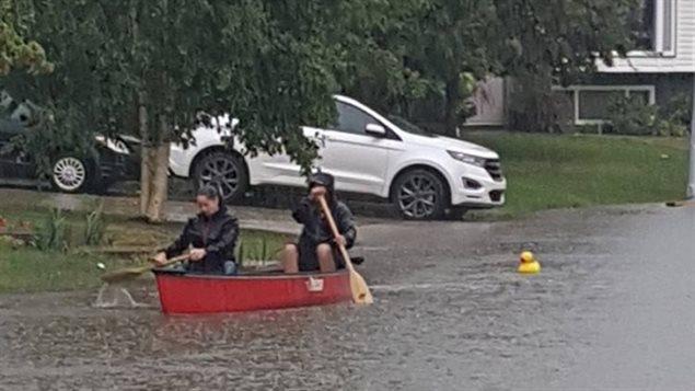 Des résidents à bord d'une barque pendant les inondations à Fort McMurray.