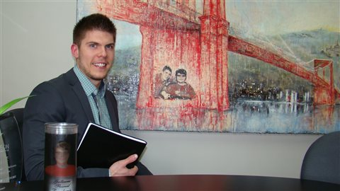 Samuel Fleurent Beauchemin at his office in Victoriaville, QC. We see him dressed in a dark suit at a desk holding a binder. In the background is a large painting of a bridge. The near support of the bridge has a rendering of the photo of the Beauchemin brothers at the top of the story.
