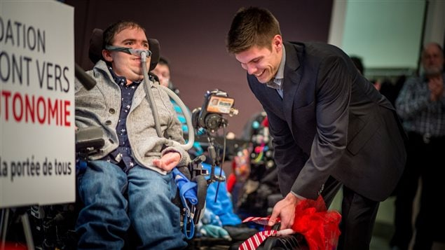 Samuel Fleurent Beauchemin helps Philippe Desrochers, 27, who has Duchenne muscular dystrophy at a Christmas party at which the Fondation le Pont vers l'Autonomie gave out two robotics arms as gifts. We see Beauchemin on the right standing, wearing a dark suit and wide smile below his dark crew-cut hair. He is reaching down with his left hand to adjust something at the foot of Desrochers's wheelchair. Desrochers wears a breathing apparatus and a light sports jacket and grey pants. Attached to the front of the wheelchair is a robotics arm, which is long and thin with what appears to be a tiny computer at its top.