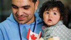 Un réfugié syrien et sa fille lors de leur arrivée à Toronto, en décembre 2015