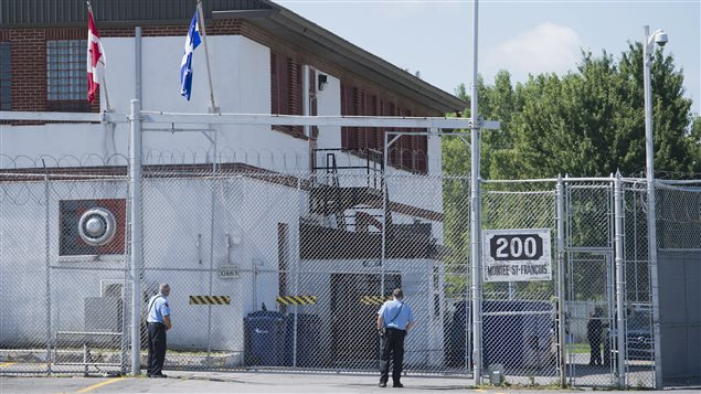 Guards stand outside the gates of an immigrant holding centre in Laval, Que., Monday, August 15, 2016.