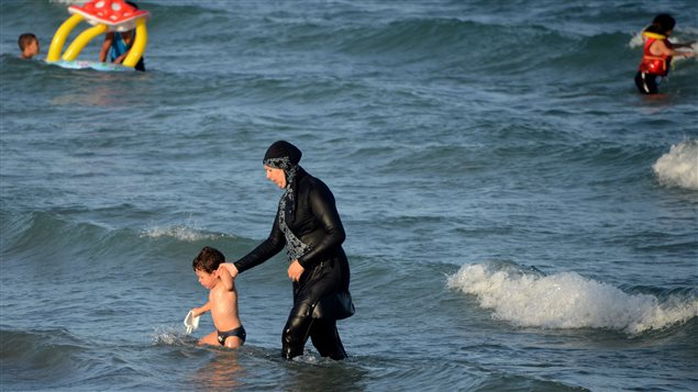 Une femme en burkini se baigne.