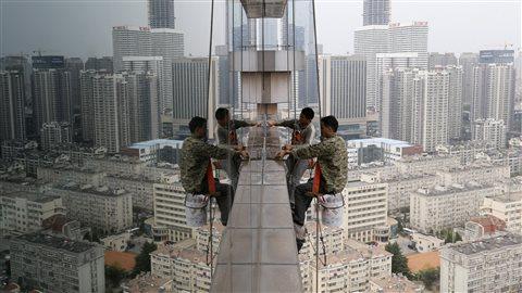 Des travailleurs nettoient les fenêtres en verre d'un bâtiment de 30 étages à Qingdao, en Chine.Crédit photo : China Stringer Network/Reuters