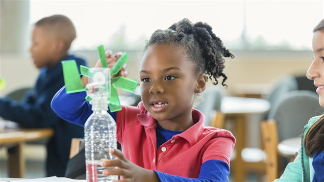 Une jeune fille bricole avec des matériaux recyclés.