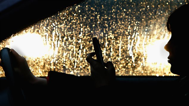 Une automobiliste utilise un téléphone cellulaire au volant.