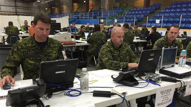 des militaires assis à leur poste de travail dans un aréna