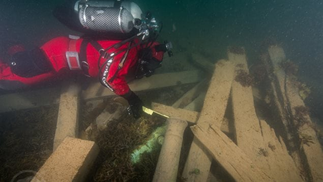 Astern of the wreck of HMS Erebus, Parks Canada underwater archaeologist Filippo Ronca measures the muzzle bore diameter of one of two cannons found on the site, serving to identify this gun as a ''brass 6-pounder''