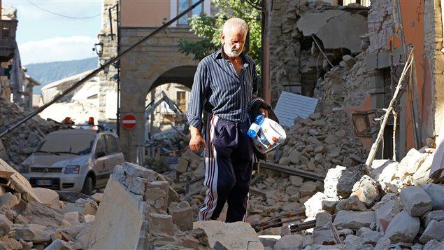 Un homme marche dans les d�combres � la suite du tremblement de terre d'Amatrice.