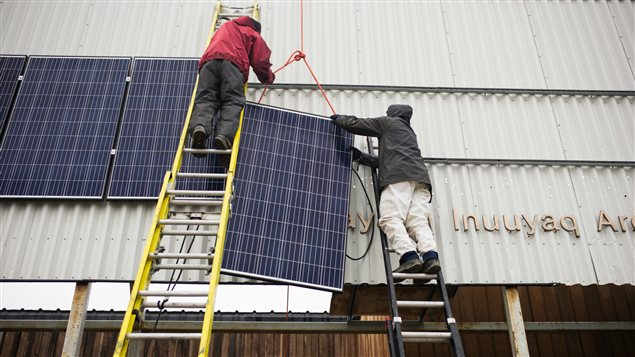 Vancouver Renewable Energy Coop Solar Installer, Duncan Martin (L) and Logistics Coordinator for Greenpeace Canada, Claude Beausjour install solar panels at the Clyde River community centre.
