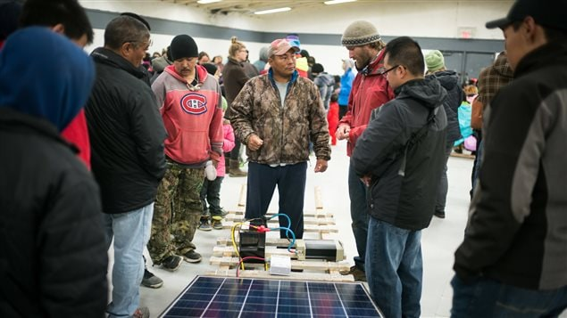 Lootle Arreak (in red) and Esa Quillaq (in camouflage) speak with Vancouver Renewable Energy Coop Solar Installer, Duncan Martin about solar panels, at Clyde River community centre. Greenpeace has come to deliver solar panels and offer a series of lectures and workshops in Clyde River.