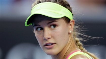 Eugenie Bouchard continues the hunt for her game that's pretty much gone missing over the last two years. We see her looking backwards with a slightly bewildered look in her eyes. Her blond hair is in a braid. She wears a yellow cap.