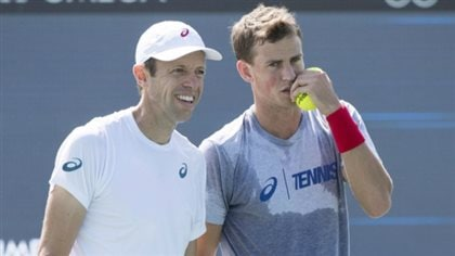 There's talk that Daniel Nestor (left) and Vasek Pospisil have a legitimate shot at the men's doubles title in New York. We see the two sweating and planning strategy with Nestor smiling and Pospisil speaking behind a pair of yellow tennis balls he holds in his left hand.