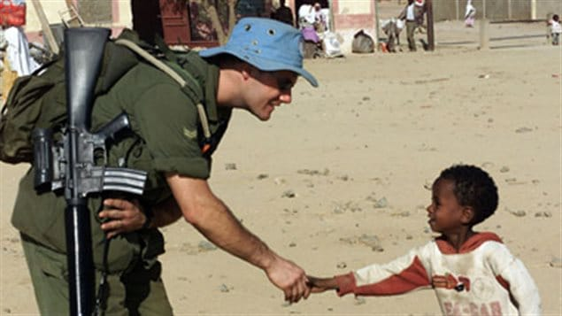 A Canadian soldier meets a young Eritrean during a familiarization patrol north of the TemporarySecurity Zone, as part of Operation Eclipse,Canada's contribution to United Nations Mission inEthiopia and Eritrea, 2001.
