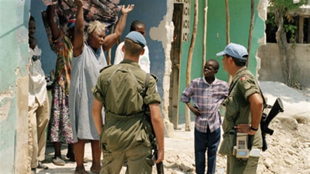 May 8, 1997, Port-au-Prince: UN peacekeepers from the Canadian Battalion, part of the United Nations Support Mission in Haiti (UNSMIH), talking with an upset Port-au-Prince woman. Peacekeeping now requires a much wider skill set of members beyond military tactics.