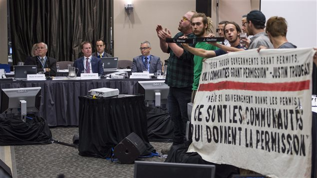 Demontstrators entered the hearing room, displayed a banner and made noise to disrupt proceedings.
