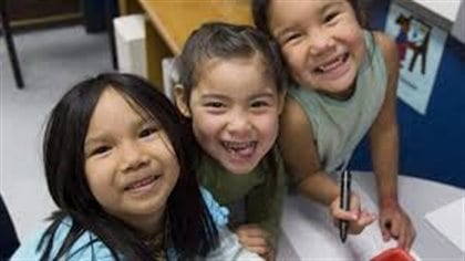 Cindy Blackstock says too many First Nations children are continuing to fall behind children in the rest of Canada. We see three pre-school girls looking up and grinning widely at the camera.