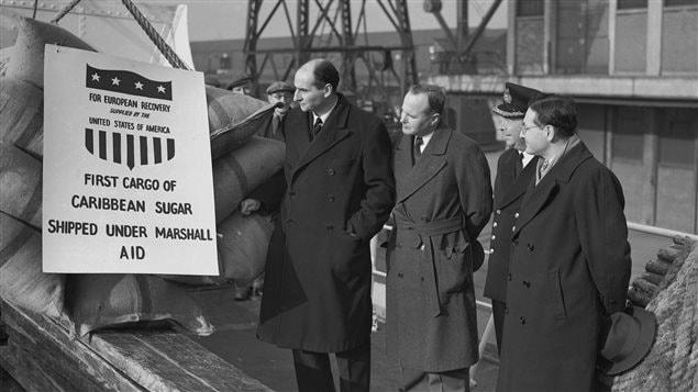 Des dignitaires assistent à l'arrivée de sacs de sucre envoyés en Europe dans le contexte du plan Marshall