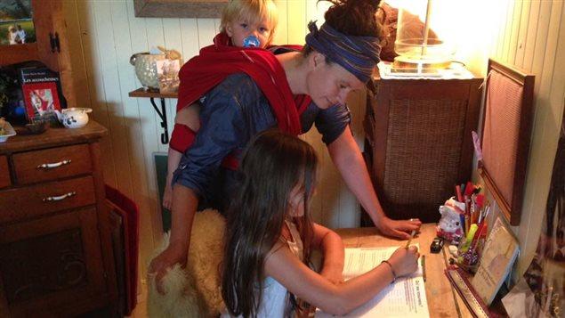 Trichat Hamel, la maman ''enseignante'', Evangeline 9 ans scolarisée à la maison depuis la première année et Theodore 2 ans, que sa maman porte dans le dos.