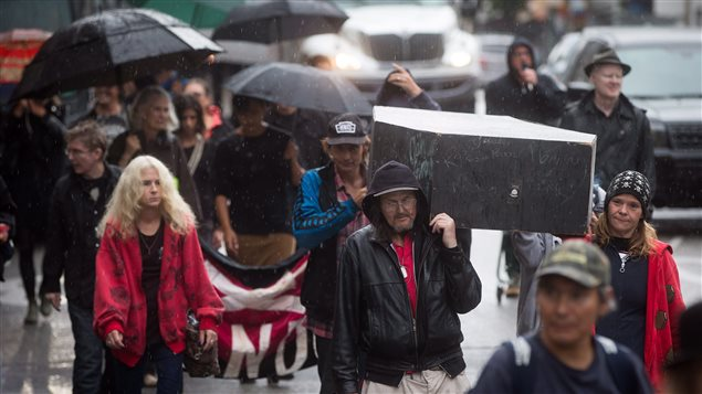 People carried a coffin to remember friends and family members who have died of overdoses on Overdose Awareness Day in Vancouver yesterday.