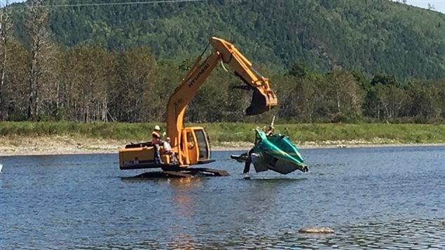 L'excavatrice sort l'hélicoptère de l'eau