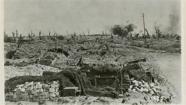 An artillery shell bursts in a blasted landscape at Hill 70. A Canadian soldier can be seen in what is likely a former German howitzer gun pit which has a net draped over it, presumably to conceal it from possible spotter planes. Part of the wheel and gun trail can be seen, possibly a 21-cm gun, with the wheel of what may be a  limber on the far side of the pit.