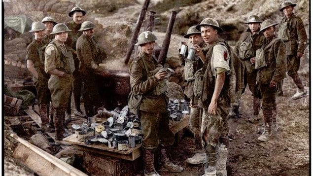 Colourized image of original black and white photo showing a soldier slightly wounded in shoulder and leg drinking tea about 100 yards behind the front line at Hill 70, Aug.1917