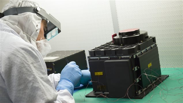 The Canadian laser mapping technology is about the size of a microwave oven. A technician prepares the OLA sensor head for testing at NASA's Goddard Space Flight Center in Baltimore, Maryland.