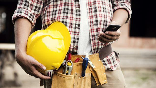 Un homme utilise son téléphone intelligent sur un chantier de construction.