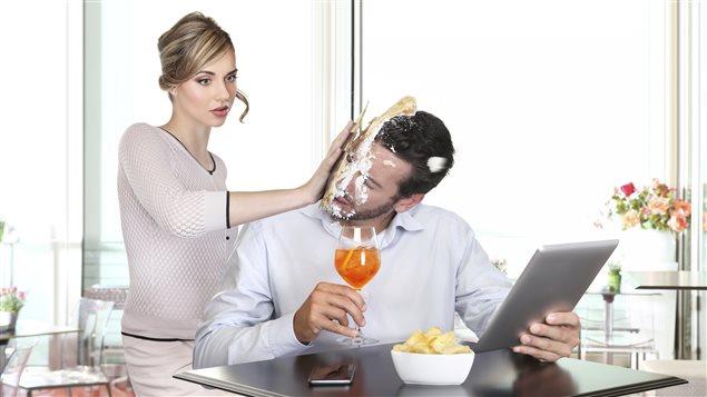 Une femme lance un gâteau au visage d'un homme assis à une table