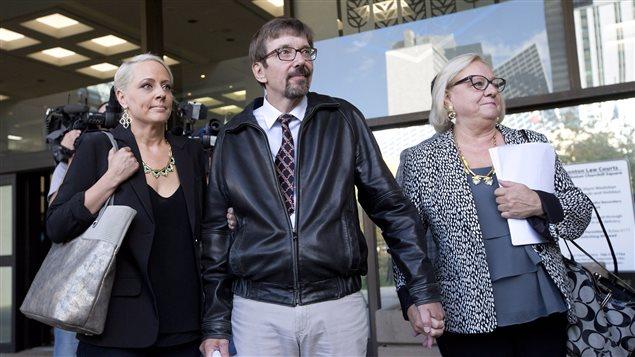 Deux femmes et un homme sortent d'un palais de justice