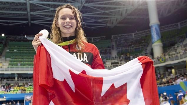 La nageuse canadienne Penny Oleksiak pose avec le drapeau canadien lors des Jeux olympiques de Rio en 2016.