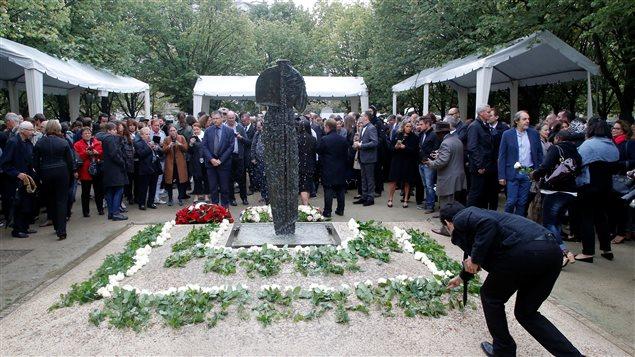 Un homme dépose des fleurs pendant la cérémonie de commémoration des victimes à l'Hôtel national des Invalides.