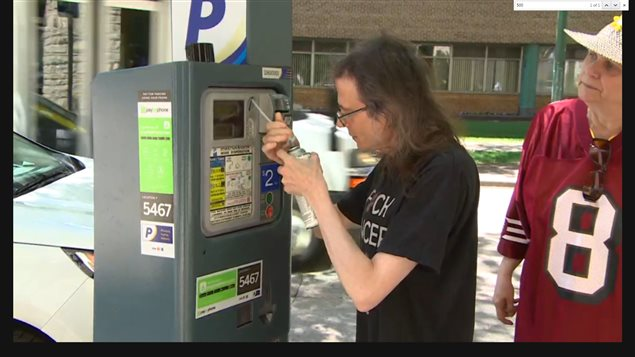 Protesting parking fees at hospitals, Collin Kennedy uses a tin of insulating foam, which will harder to a solid mass, to fill and block the coin slots in a parking machine at the cancer treatment centre in Winnipeg