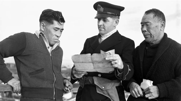 A Royal Canadian Navy officer examines ownership documents before announcing the confiscation of the Japanese-Canadian's fishing boat in 1941