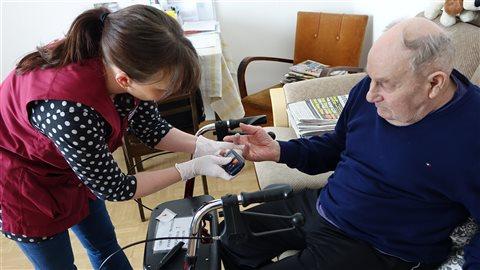 Une infirmière rend visite en septembre 2016 à un Québécois atteint d'Alzheimer.