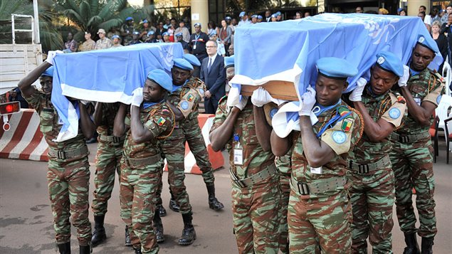 UN peacekeeping force soldiers carry coffins covered with United Nations flag at Bamako on february 17, 2016, at the last tribute to seven guinean UN soldiers killed on february 12 during a jihadist attack against their camp at Kidal.