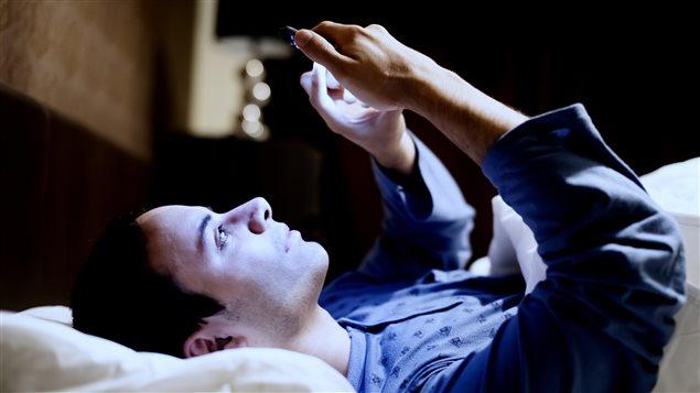 Un homme consulte son t�l�phone dans son lit.