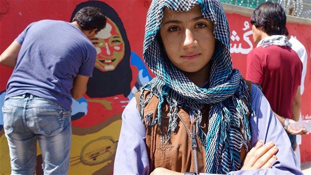 Omeid Sharifi, de dos, en train de peindre une murale qui montre le visage de Moursal, rescap�e d�un attentat.