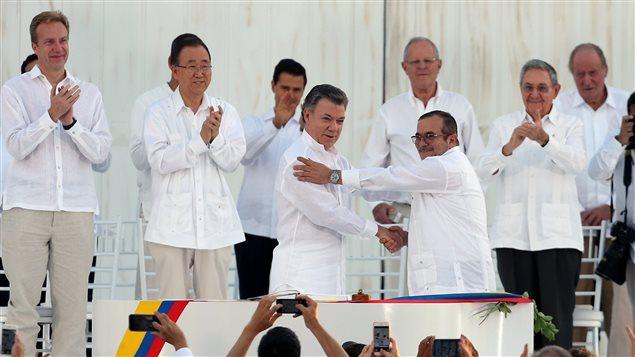 Poign�e de main entre le pr�sident Juan Manuel Santos (g) et le chef des FARC Rodrigo Londono scellant le trait� de paix.