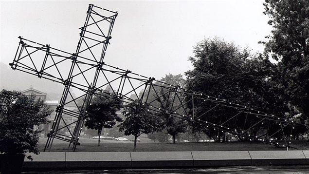 Cette r�plique renvers�e de la croix illumin�e du Mont-Royal, oeuvre de Pierre Ayot, appartenait au projet Corridart organis� par le comit� des Jeux olympiques de Montr�al en 1976. Elle a �t� d�mantel�e � la veille des Jeux, sur ordre du maire Jean Drapeau qui la jugeait ind�cente.