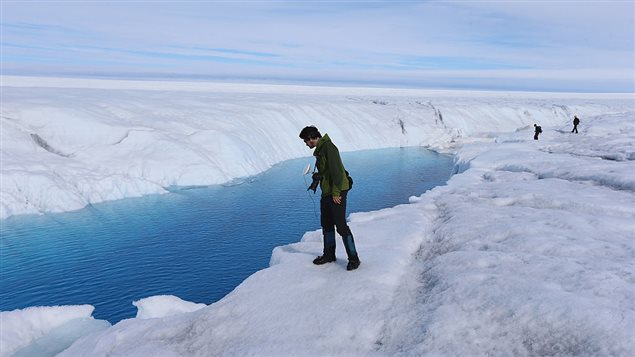 David Shean a Ph.D. student at the University of Washington looks at a meltwater stream on July 16, 2013 on the Glacial Ice Sheet, Greenland.