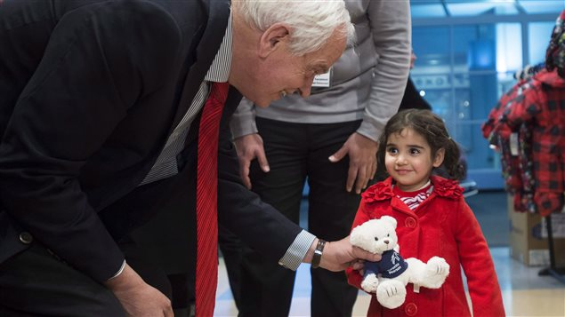 Immigration Minister John McCallum (left) greets newcomers at Toronto's airport on February 29, 2016. He wants to increase immigration levels in the future.