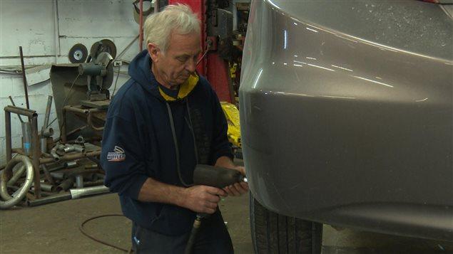 Un mecánico canadiense cambiando las ruedas de un auto.