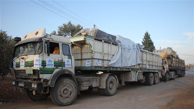 Des camions transportant de l'aide sur une route dans la ville d'Orum al-Kubra, près d'Alep.