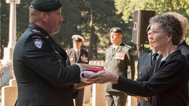 Lieutenant Colonel Ken McClure, Commanding Officer of The Algonquin Regiment, hands the Canadian Flag to Judith Thomas, a second cousin of Private Kenneth Duncanson during a burial ceremony at the Adegem Canadian War Cemetery, near Brugge, Belgium, on September 14, 2016. Private Duncanson died exactly 72 years ago during the Second World War