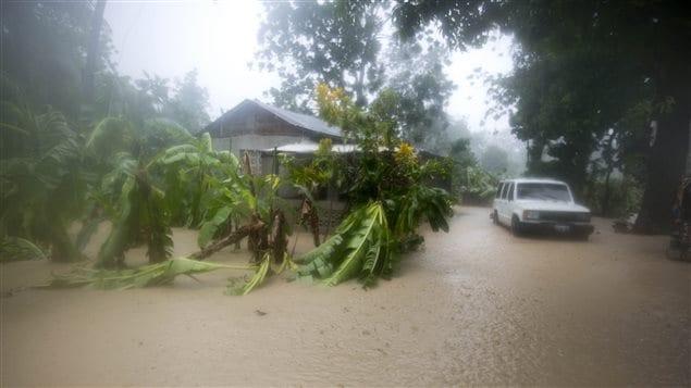 Un véhicule tente d'avance dans l'eau qui inonde la route, à Léogâne, en Haïti.
