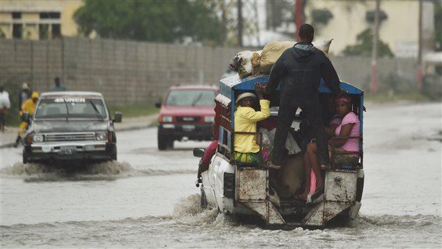 Un autobus se fraie un chemin dans une inondation.