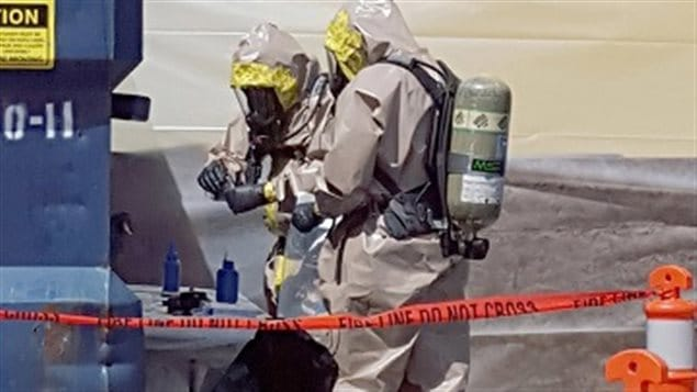 June 27, 2016, RCMP in hazmat suits in Vancouver inspect containers (bliue bottles on table) containing deadly carfentanil. The plastic bottles were shipped from China labelled as printers ink to avoid inspection by border control agents.